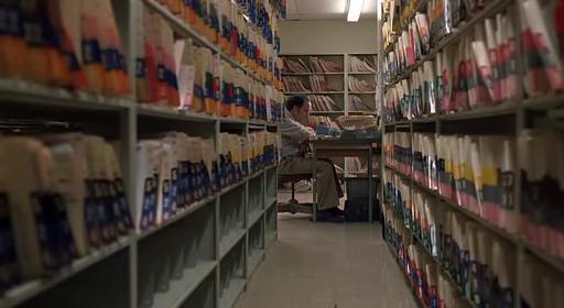 Harvey Pekar, interpretado por el actor Paul Giamatti, en su mesa entre las asfixiantes estanterías del archivo de historias clínicas activas.